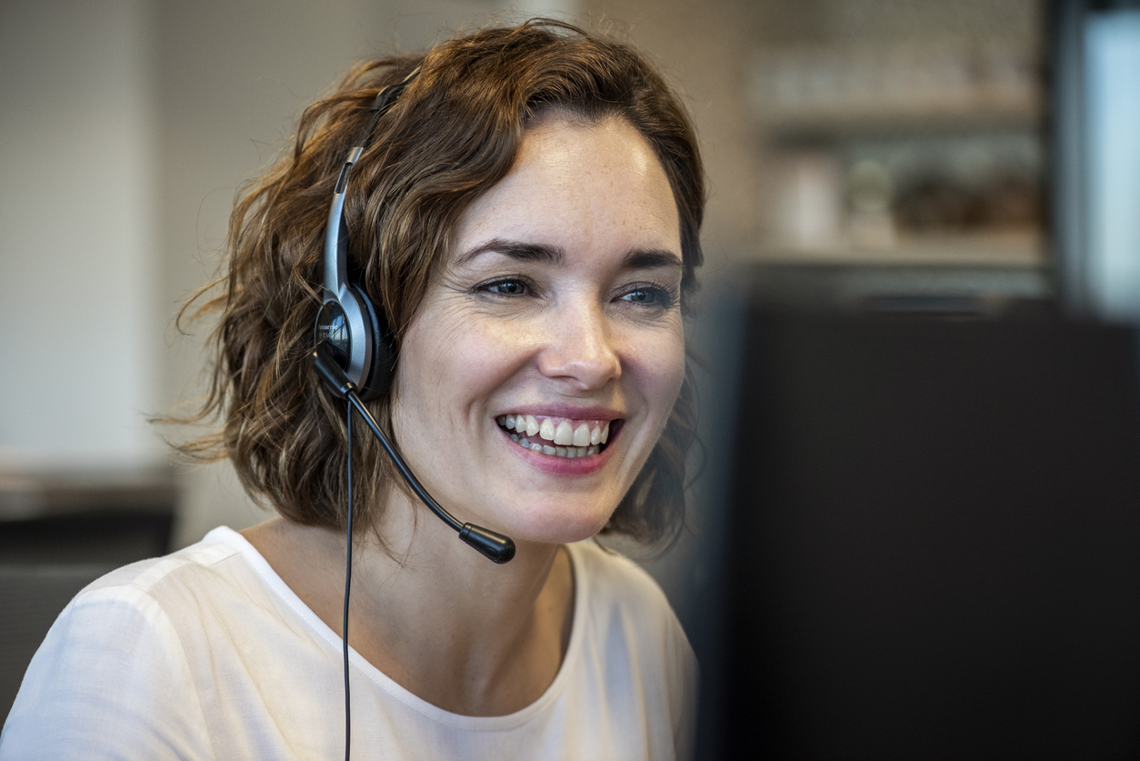 woman in a call center wearing a headset smiling as she talks to a customer and looks at her computer