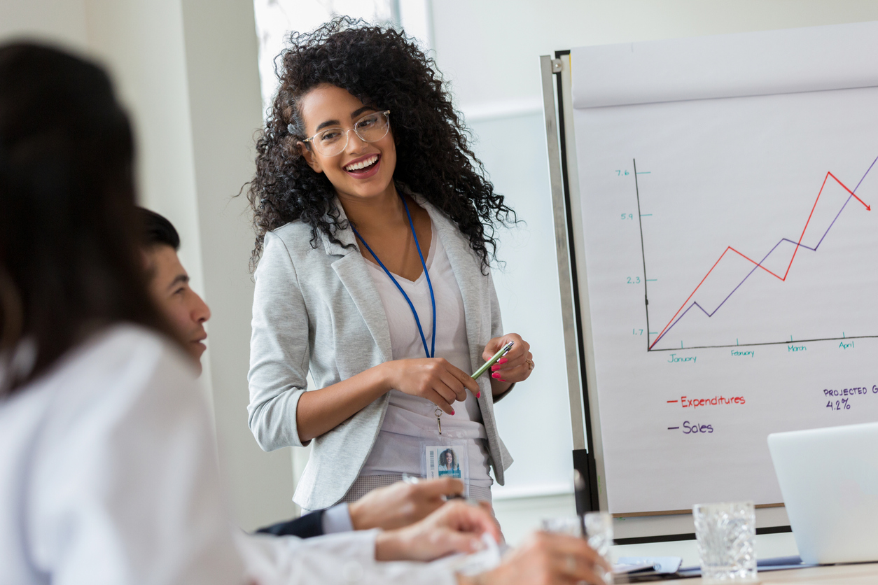 saleswoman smiling at colleagues looking at a sales graph