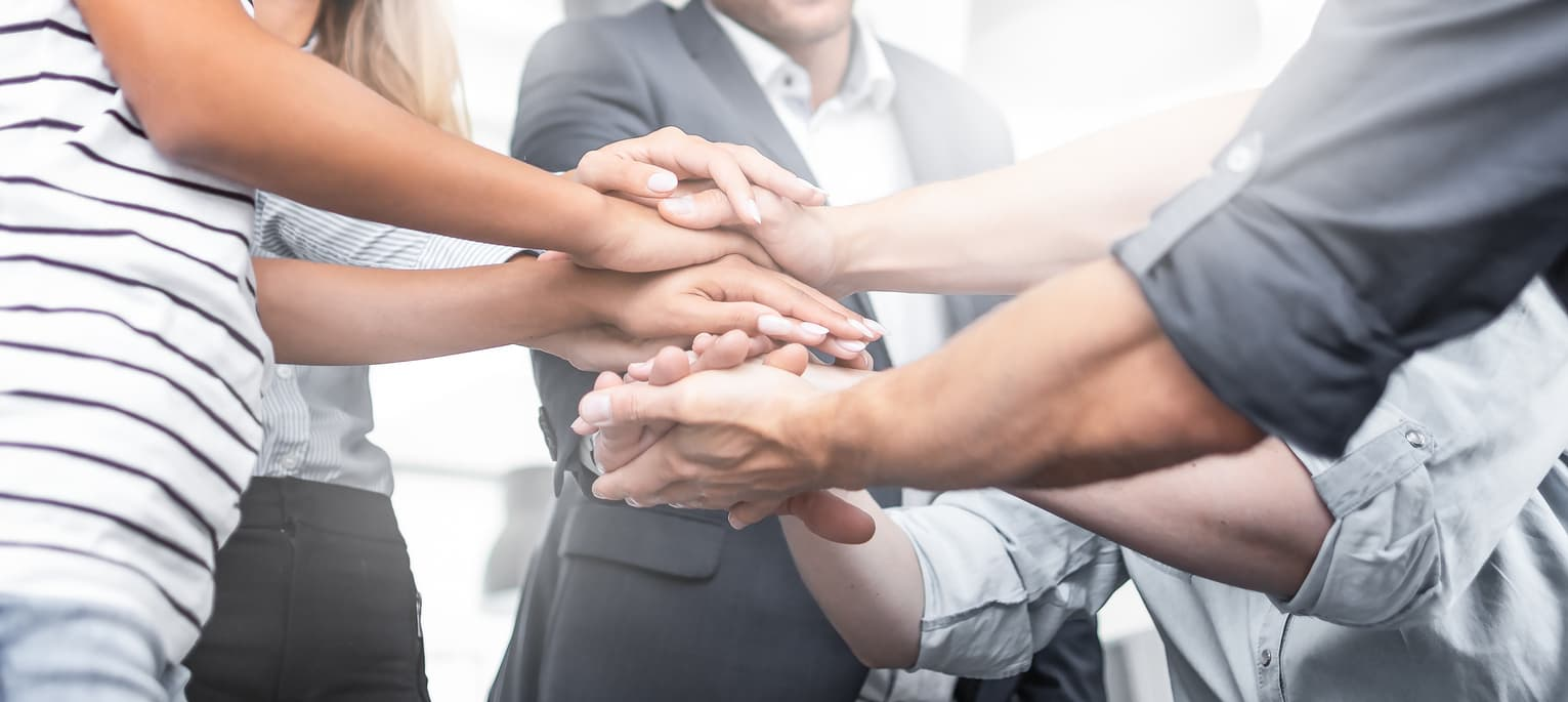Five people standing in a close circle with their hands stacked one on top of each other in a display of supportive, positive company culture.